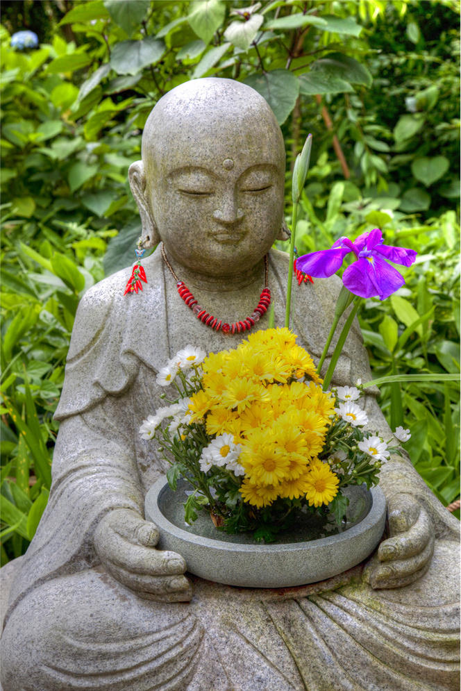 Buddha statue holding a basket of flowers.
